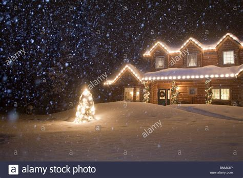 picture with lights log home decorated with lights with snow falling
