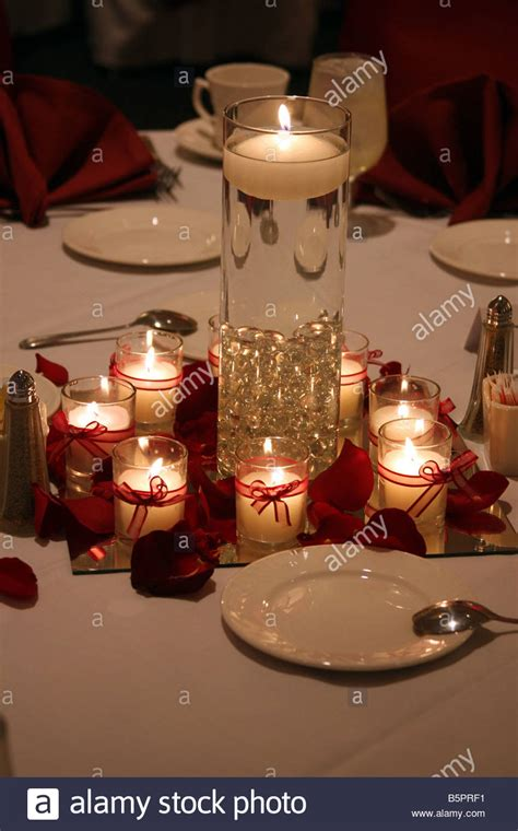 floating candle centerpiece burning candles and a floating candle in a vase as the