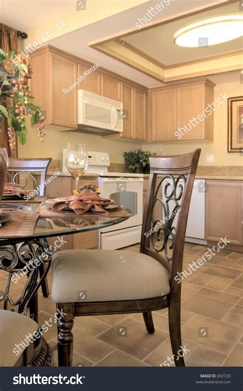 kitchen island table with 4 chairs modern kitchen with island table four chairs fridge stove and ceiling fan stock photo 692729