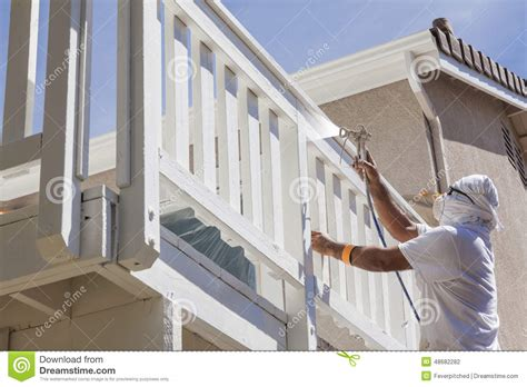 spray painter house house painter spray painting a deck of a home stock photo