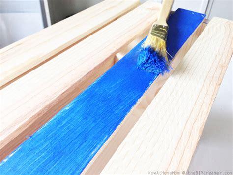 spray painting untreated wood crate on wheels diy storage tutorial