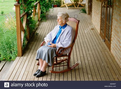Old Woman Sitting In Rocking Chair On Veranda At Home