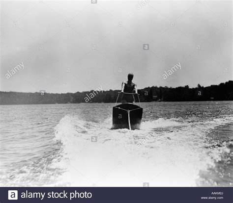 Board Behind Boat by 1930s Woman Aquaplaning Water Board Being Towed Behind
