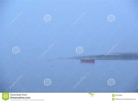 Crescent Roeiboot by Een Eenzame Rode Roeiboot Of Een Skiff In Zware Mist Stock