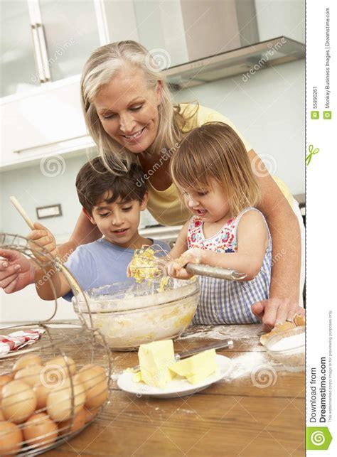petits enfants aidant la grand m 232 re 224 faire des g 226 teaux cuire au four dans la cuisine photo