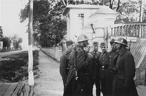 German and Slovak soldiers talk on the street of an ...