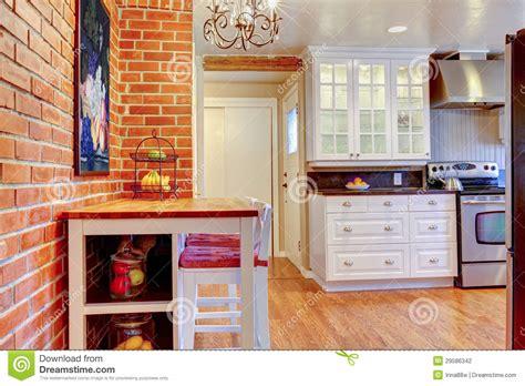 la cuisine blanche avec le mur de briques le bois dur et