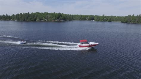 Fast Boat Videos by 4k Aerial Fast Boat Pulls Tube With Two People Stock Video
